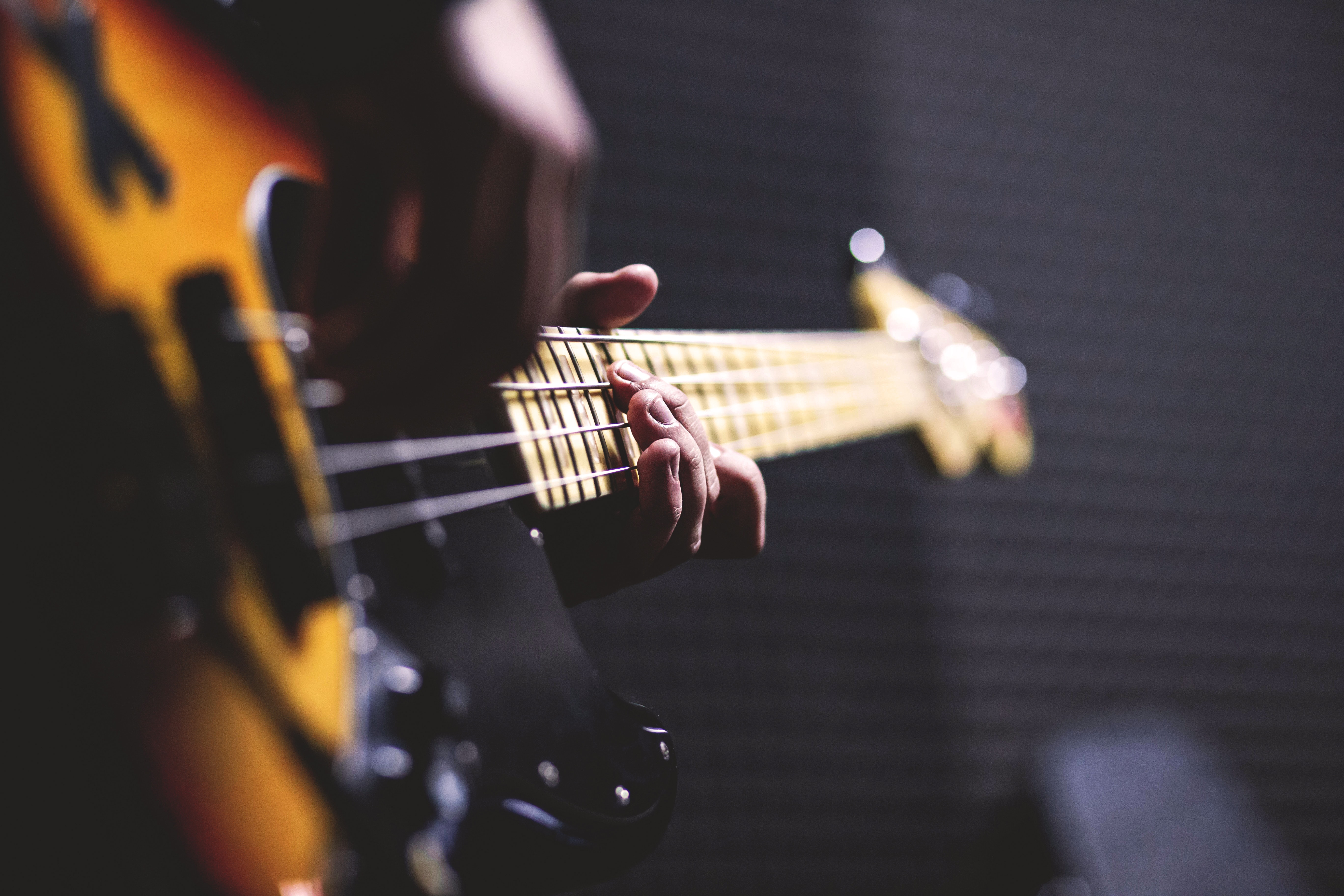 Person Playing Sun Burst Electric Bass Guitar in Bokeh Photography by freestock.org